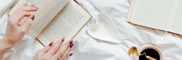 Woman reading a novel on her bed on a sunday afternoon