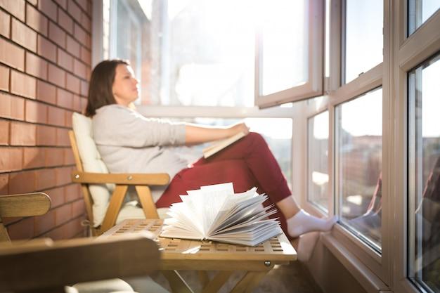 暖かい晴れた日にバルコニーで読書する女性