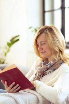 Женщина читает на диване