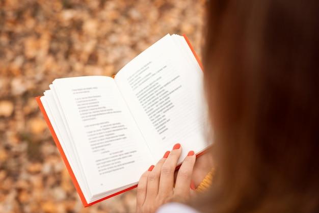 Стихи чтения женщины в осеннем парке. вид открытой книги с красной крышкой в руках девушки сзади сзади.