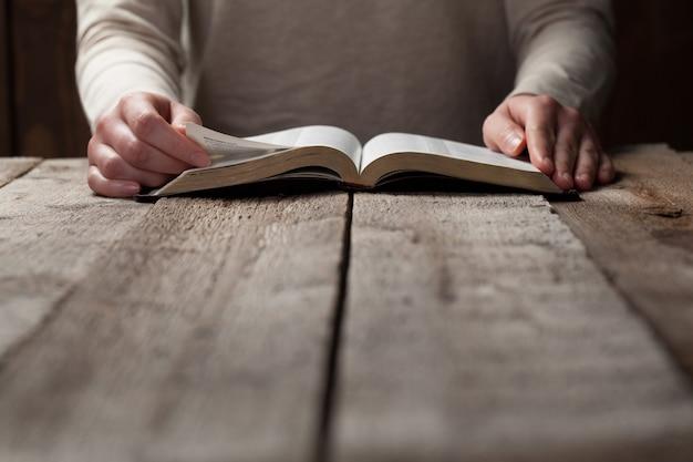 나무 테이블 위에 어둠 속에서 성경을 읽는 여자