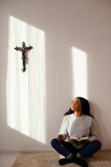 Женщина читает библию в помещении