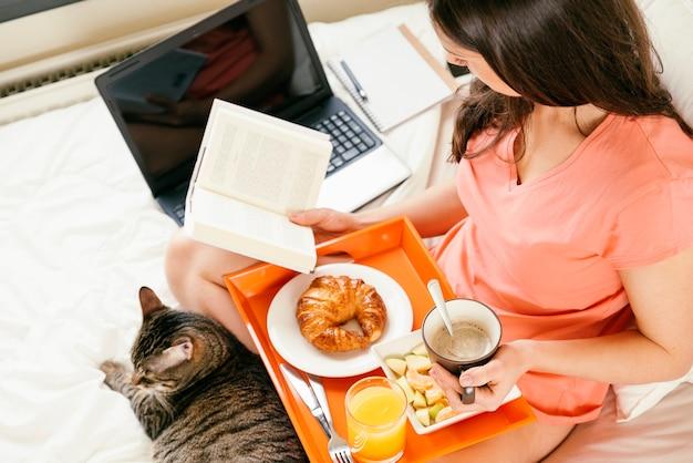 Женщина читает книгу и завтракает со своим сладким котом.