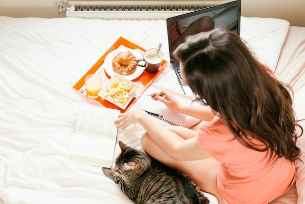 Женщина читает книгу и завтракает