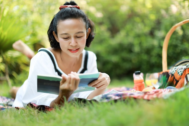 Женщина читает книги о ткани в естественном саду. концепция пикника.
