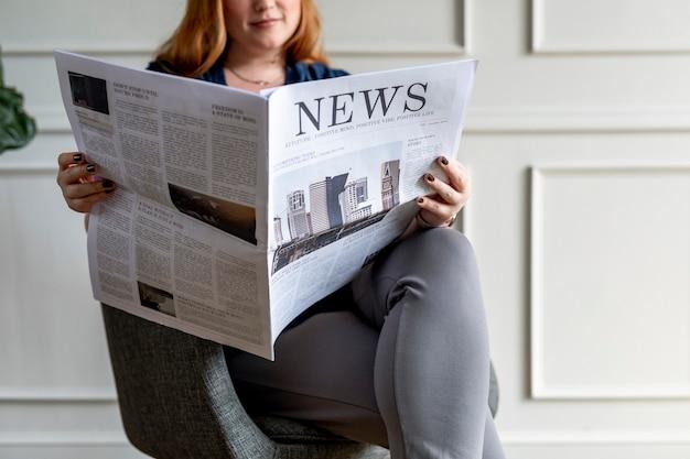 家で新聞を読んでいる女性