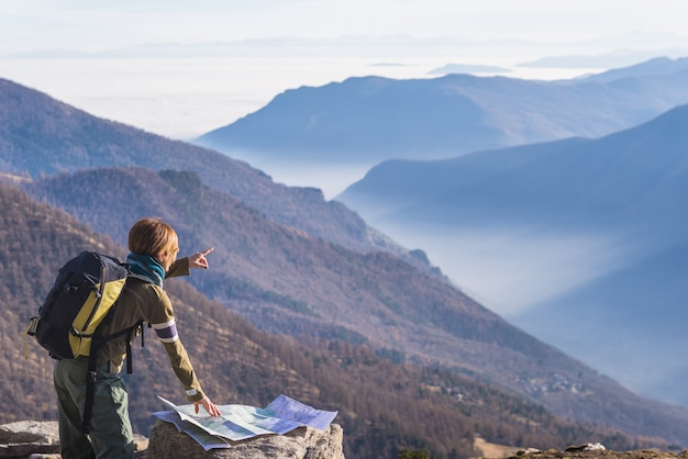 Woman reading trekking map and poiting finger to the alps