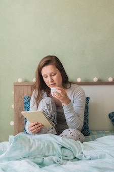 女性がベッドにいる間読書