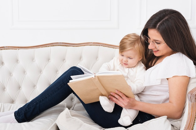 Woman reading with baby on sofa