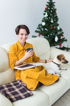 Woman reads book in front of christmas tree with dog jack russell terrier. christmas, holidays and