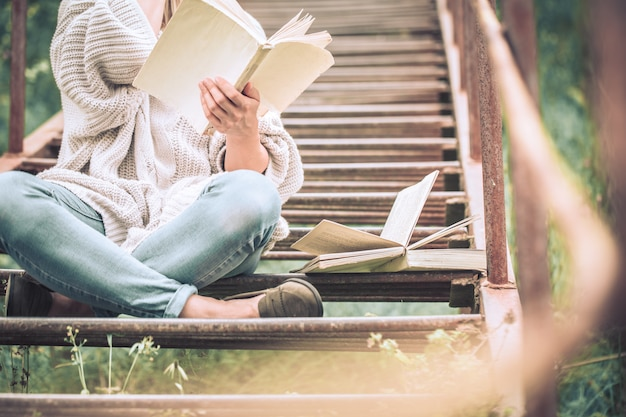 Woman reads a book on the steps of a staircase