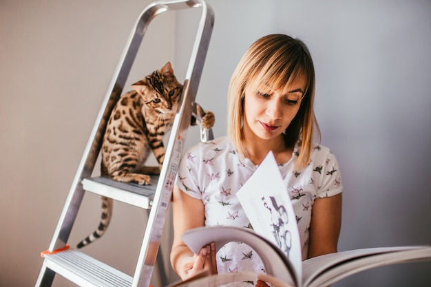 Woman reads a book while bengal cat stands on the ladder behind her