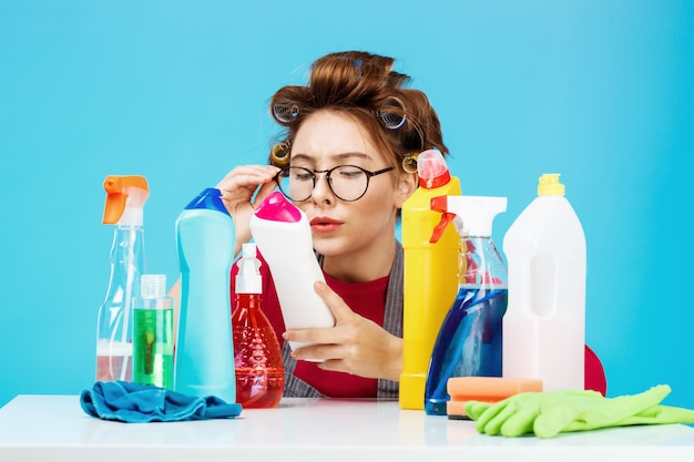 Woman reads details on bottle while doing housework, she looks tired