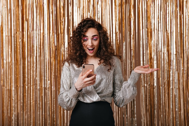 Woman reads message in phone and posing surprised on golden background