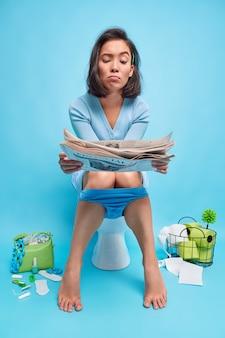 女性は不幸な表情で新聞を読むバスルームの便器のポーズに座って青のニュースを見つける自分自身を明らかにする