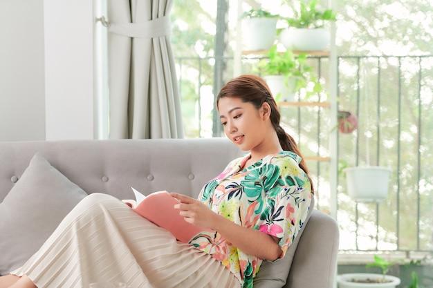 女性は灰色のソファに横たわって本を読む