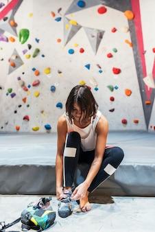 屋内の人工壁でロッククライミングを練習する準備ができている女性。アクティブなライフスタイルとボルダリングのコンセプト。