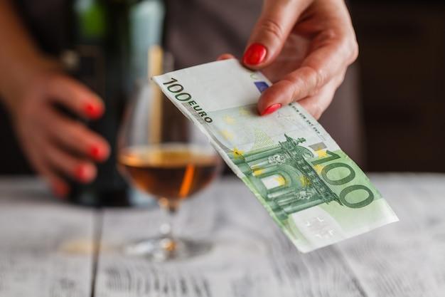 유로 지폐와 위스키를 지불 할 준비가 여자