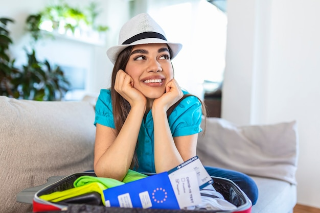 Woman ready to travel during coronavirus smiling over her suitcase at home with her passport ready