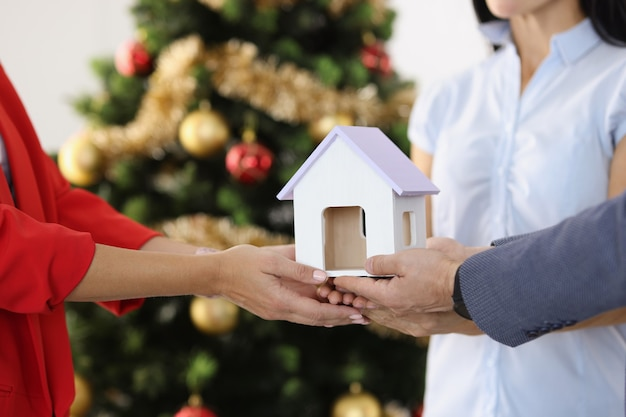 Woman realtor hands toy house to couple against background of new year tree buying property for