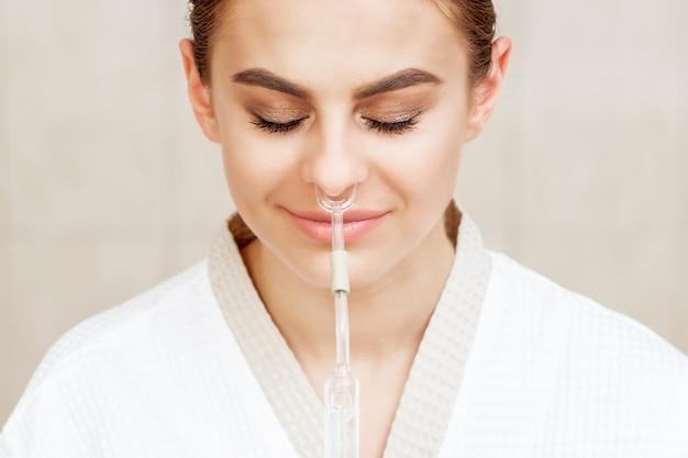 Женщина получает ингаляцию через нос.