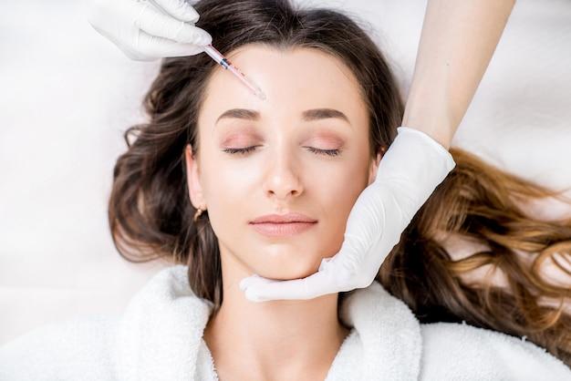 Женщина получает инъекцию ботокса в зону вокруг глаз, лежа в халате на медицинской кушетке