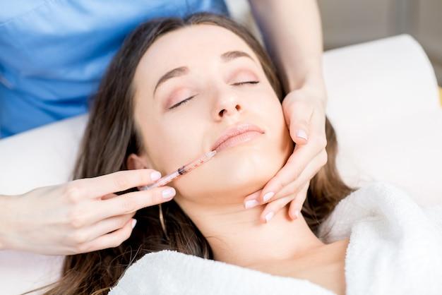 의료용 소파에 누워 입술 부위에 보톡스 주사를 맞는 여성