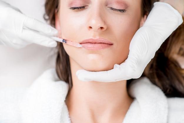 Женщина получает инъекцию ботокса в зону губ, лежа на медицинской кушетке