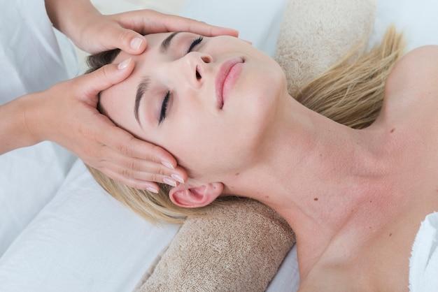 Женщина получает массаж лица в спа