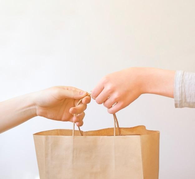 Женщина получает посылку дома от курьера.