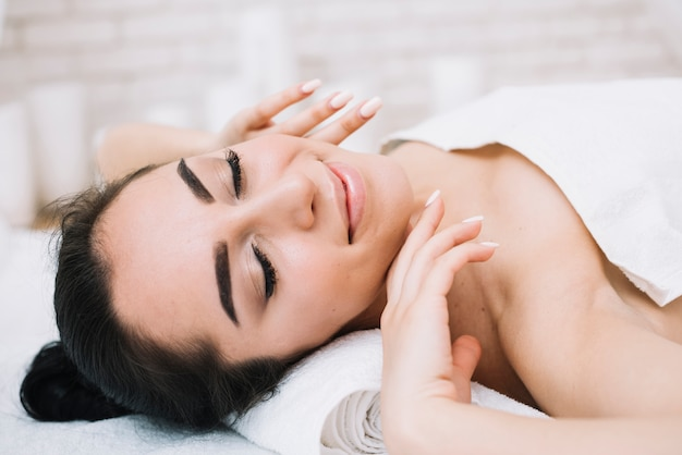 Женщина получает расслабляющий массаж лица