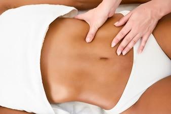 Woman receiving abdomen massage in spa wellness center.
