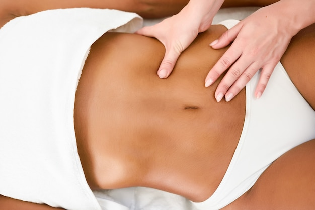 Woman receiving abdomen massage in spa wellness center.