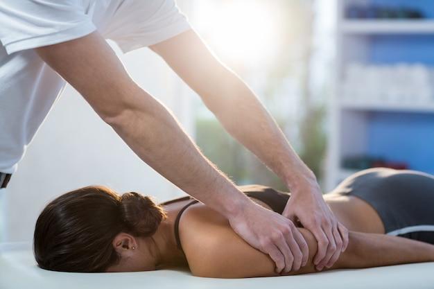 理学療法士から腕のマッサージを受ける女性