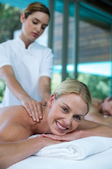 Woman receiving back massage from masseur