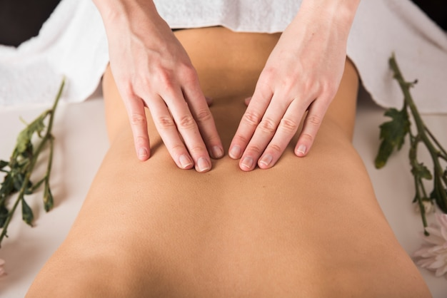 Woman receiving back massage from therapist in spa
