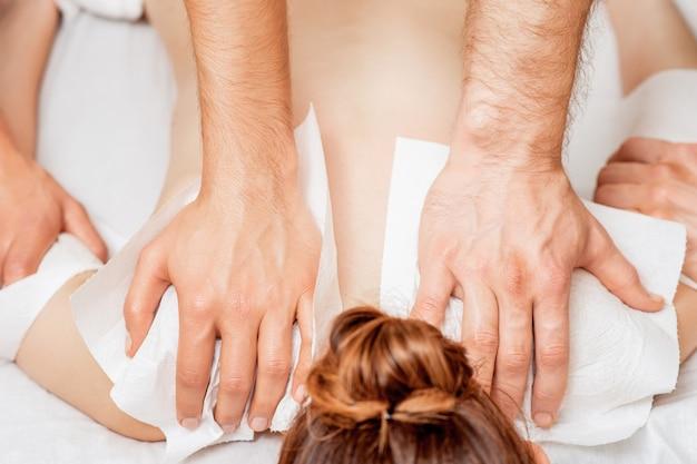 Женщина получает массаж спины в четыре руки.