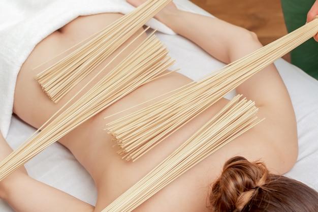 Женщина получает массаж спины с бамбуковыми вениками.