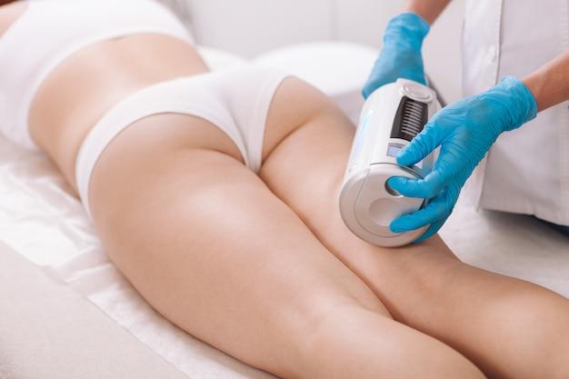 Женщина получает косметологические процедуры для тела в клинике красоты