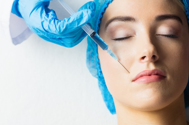 Woman receiving botox injection on her lips