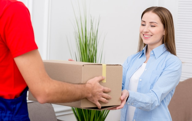 Woman receiving a cardboard box from courier