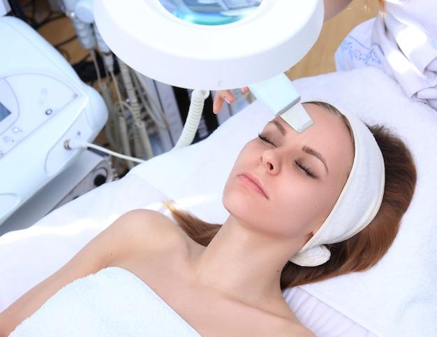 美容院でプロの超音波装置でクレンジングセラピーを受けている女性