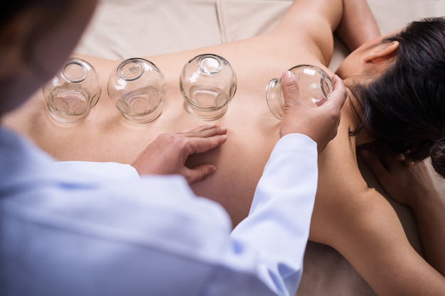 Woman receiving cupping treatment on back with doctor