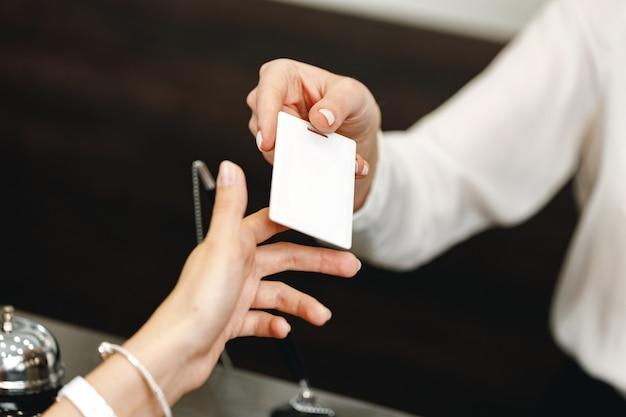 Woman receiving door key in hotel front desk close up