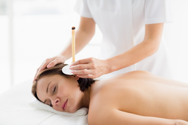 Woman receiving ear candle treatment from masseur