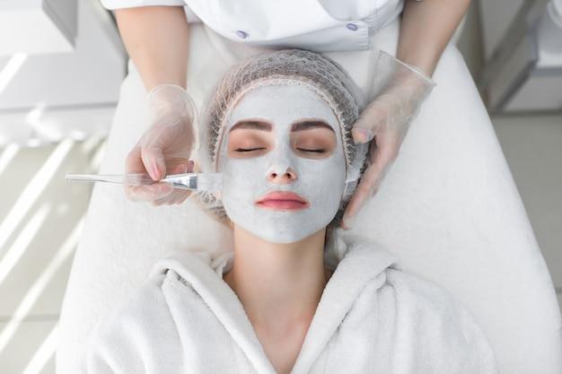 Женщина получает маску для пилинга лица