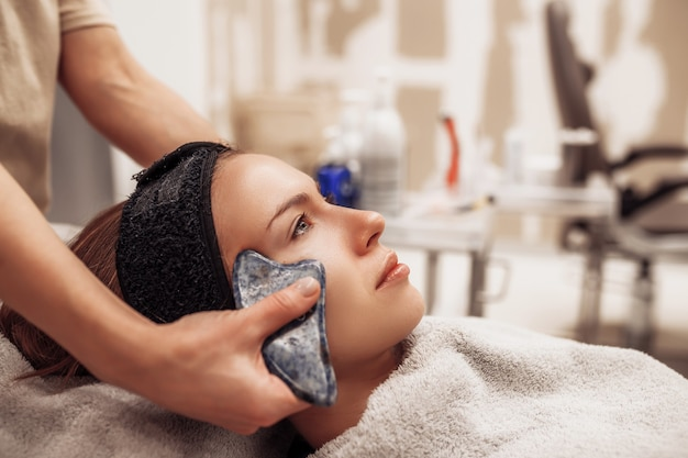 Woman receiving facial massage in beauty salon. high quality photo