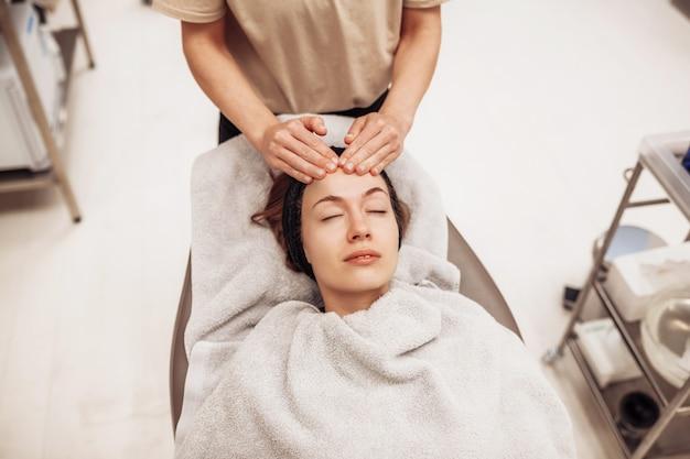 Woman receiving facial massage in beauty salon.