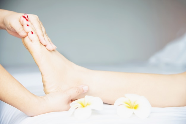 Женщина получает массаж ног от массажиста крупным планом под рукой и ногой - расслабиться в концепции обслуживания массаж массаж ног
