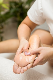 Woman receiving foot massage in spa salon